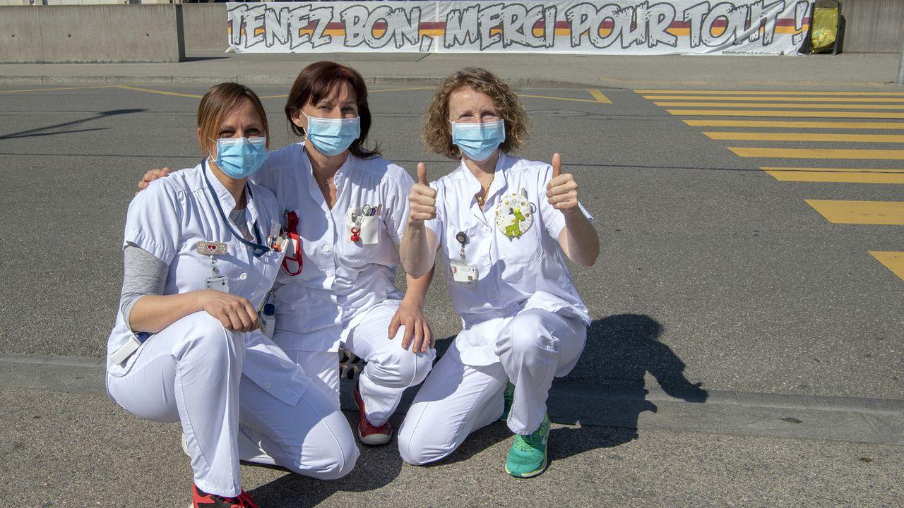 """Des infirmières des Hôpitaux Universitaires de Genève (HUG) posent devant une banderole """"Tenez Bon, Merci Pour Tout!"""": elles remercient la population de les soutenir tous les soirs à 21h00. Genève, le 19 mars 2020. [Martial Trezzini - Keystone]"""