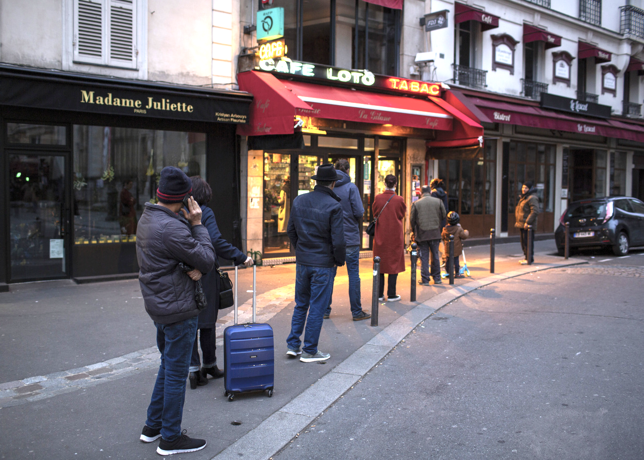 Des personnes font la queue à l'entrée d'un commerce parisien en respectant les distances.