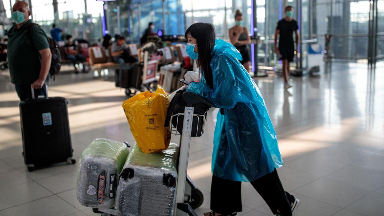 Des voyageurs dans l'aéroport de Bangkok, en Thaïlande, tentent de trouver un vol alors que la plupart sont annulés. [Jack TAYLOR - AFP]