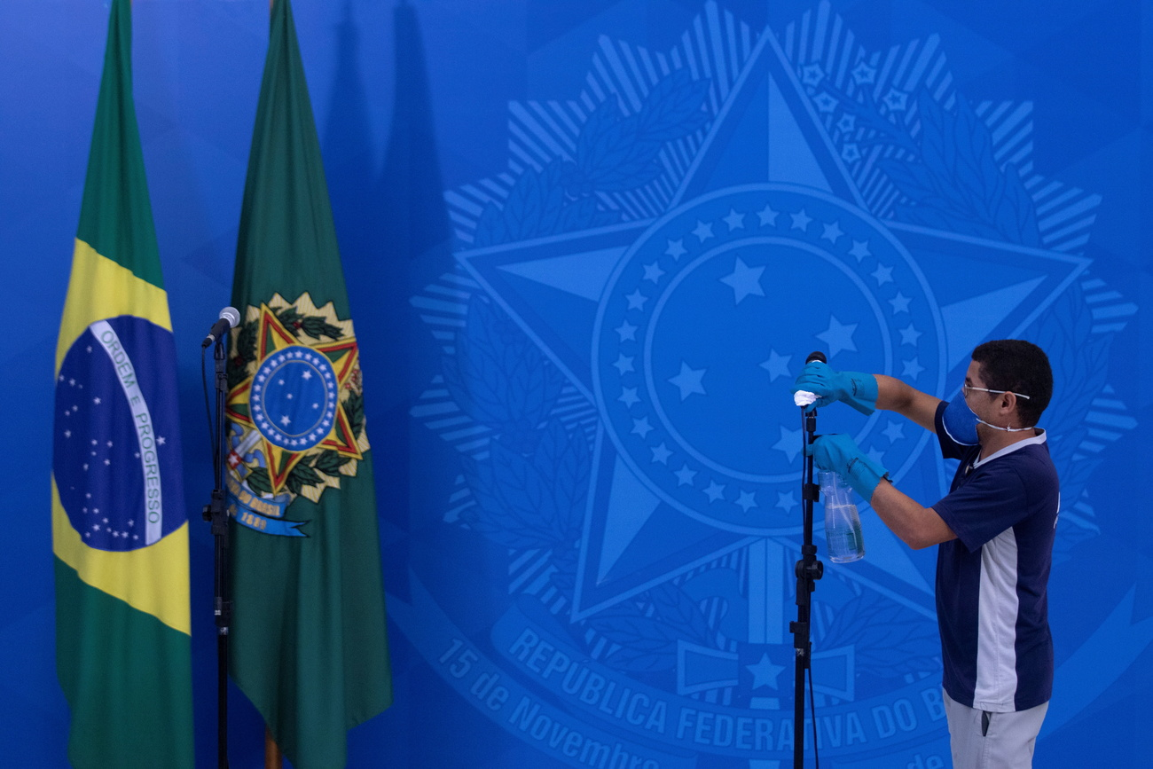 An employee disinfects the microphone before a speech by Jair Bolsonaro. The far-right president had just met with the governors of Brazil to define strategies to fight the Covid-19 in the city of Brasilia. March 23, 2020.