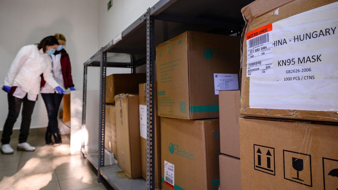 Des employées de l'Institut Pulmonaire de Farkasgyepu examinent les paquets d'équipement protecteur qui viennent de leur être livrés. Hongrie, le 31 mars 2020. [Tamas Vasvari - Keystone/epa]