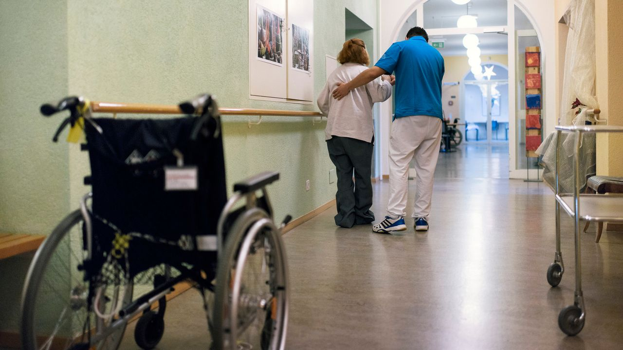 Un collaborateur d'EMS aide une résidente à marcher. [Christian Beutler - Keystone]