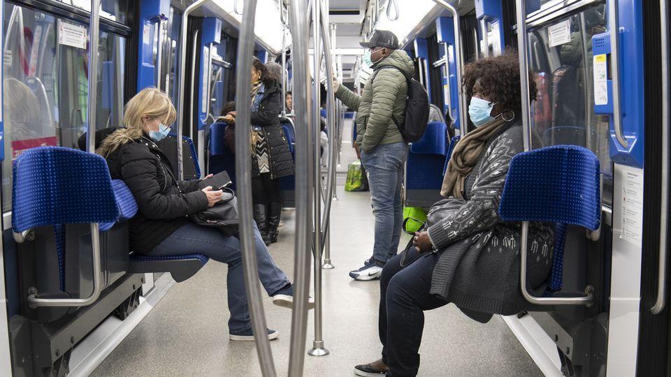Des personnes munies de masques d'hygiène dans le métro M2 à Lausanne le 23 mars 2020. [Laurent Gilliéron - Keystone]