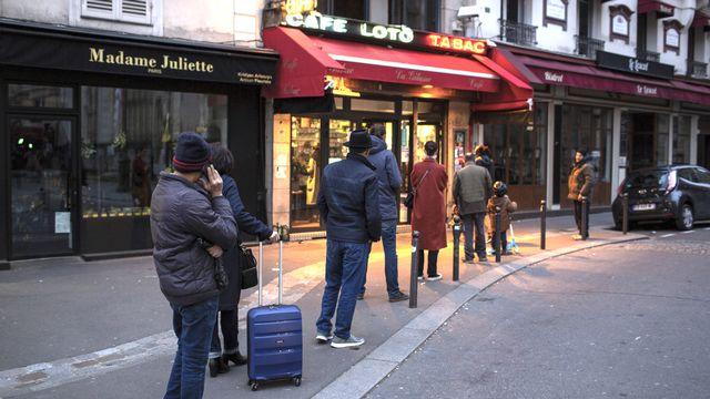 Des personnes font la queue à l'entrée d'un commerce parisien en respectant les distances. [Rafael Yaghobzadeh - AP/Keystone]