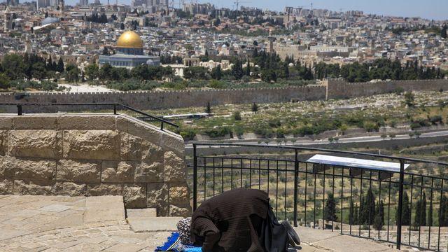 Vendredi 1er mai: une femme musulmane prie sur le Mont des oliviers à Jérusalem-Est, alors que la mosquée al-Aqsa, fermée pour cause de coronavirus, apparaît au loin. [AP Photo/Ariel Schalit - Keystone]