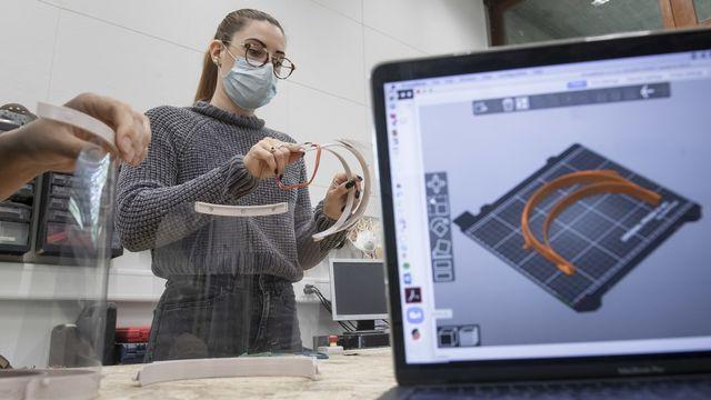 Des visière faciales de protection contre le nouveau coronavirus sont produites à l'aide d'une imprimante 3D à l'Université des sciences appliquées SUSPI à Lugano. [Ti-Press/Pablo Gianinazzi - Keystone]