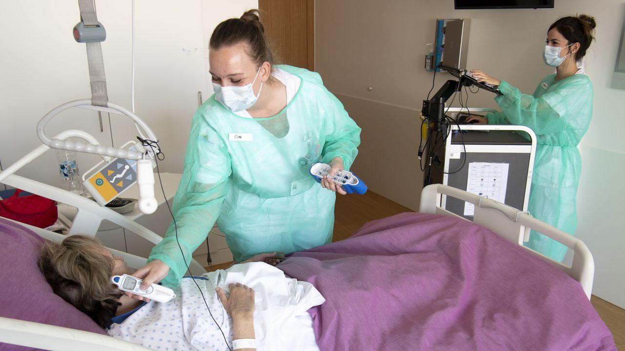 Deux infirmières au chevet d'une patiente à l'Hôpital Riviera-Chablais à Rennaz. [Laurent Gilliéron - Keystone]