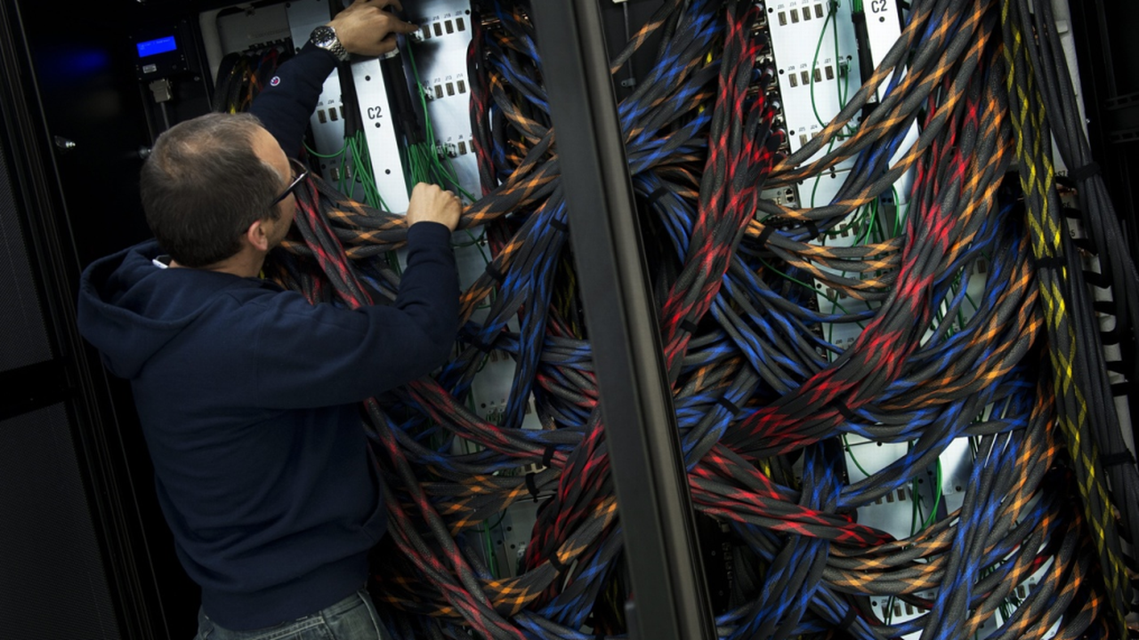 Un technicien analyse le câblage d'un super-ordinateur du CSCS à Lugano. [Gabriele Putzu - Keystone]