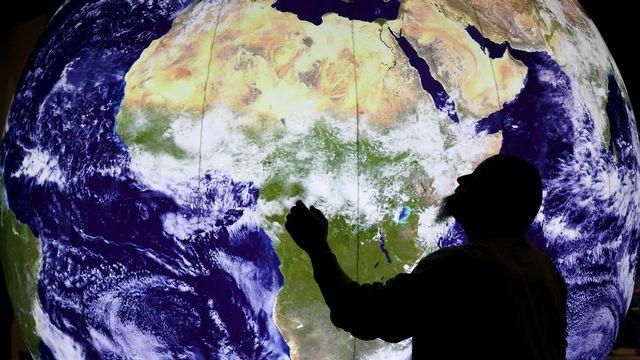 Un homme regarde un modèle de la Terre dans un musée à Berlin. [Ralf Hirschberger - dpa via AP]