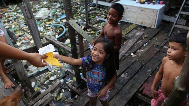 Les enfants d'un quartier pauvre de Manaus, au Brésil, reçoivent des masques de protection. [Michael Dantas - afp]
