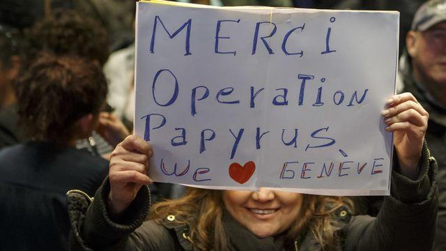 """Une femme sans-papiers montre un panneau """"Merci Operation Papyrus"""". [Salvatore Di Nolfi - Keystone]"""