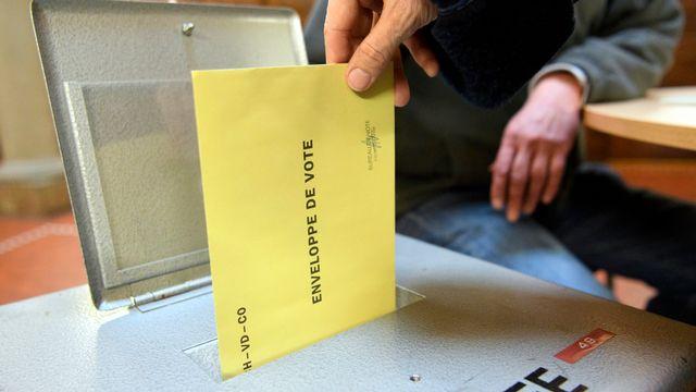 Une personne dépose son bulletin de vote dans une urne. [Laurent Gillieron - Keystone]