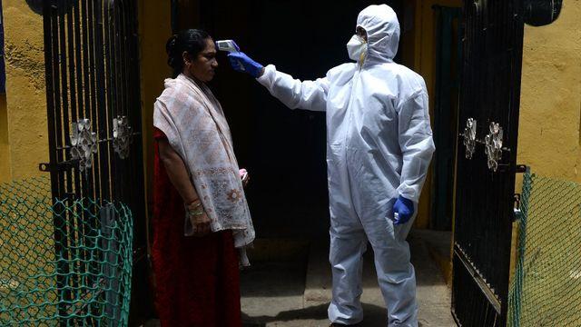 Un médecin vérifie la température d'une femme dans une zone de confinement à Chennai. Inde, le 29 juin 2020. [Arun Sankar - AFP]