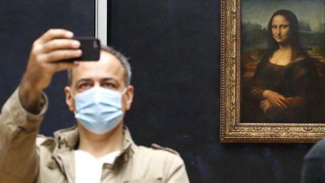 L'inamovible Mona Lisa s'amuse désormais des visiteurs masqués lui tirant le portrait au Louvre. Paris, le 6 juillet 2020. [François Guillot - AFP]