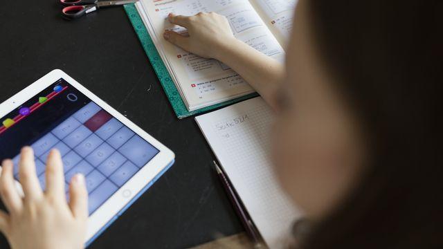 Une écolière utilise une tablette pour un exercice de mathématiques. [Gaetan Bally - Keystone]