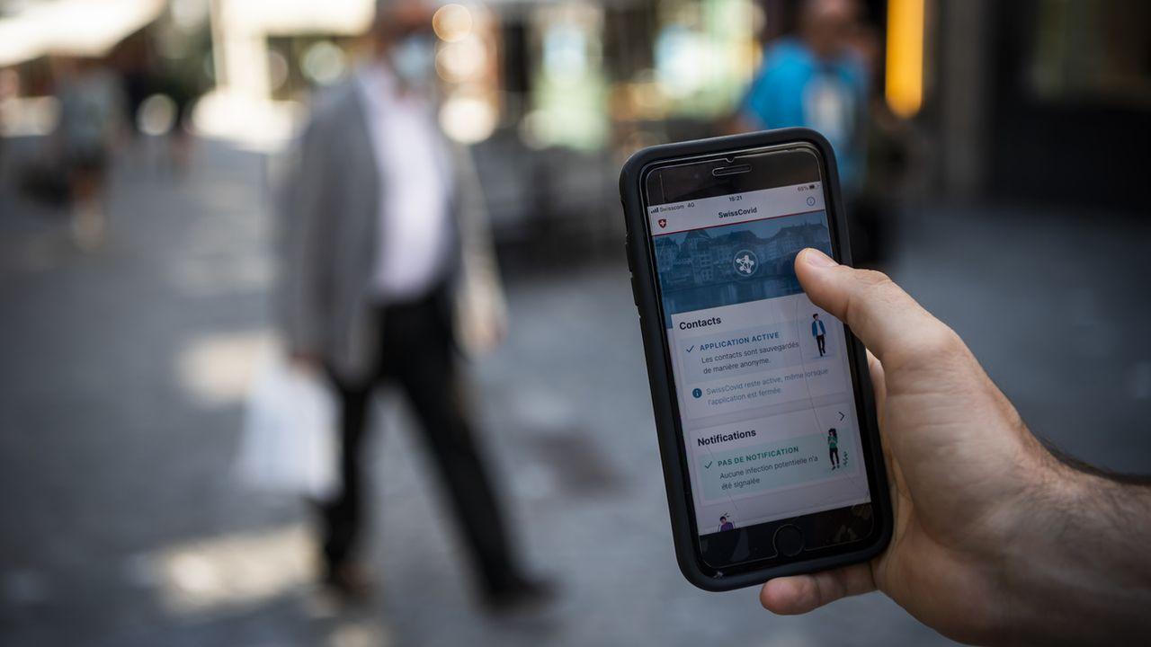 Une personne regarde sur son smartphone l'application SwissCovid. [Jean-Christophe Bott - Keystone]