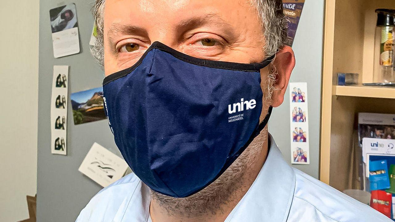 Nando Luginbühl portant un masque réutilisable offert par l'Uni de Neuchâtel. [Université de Neuchâtel]