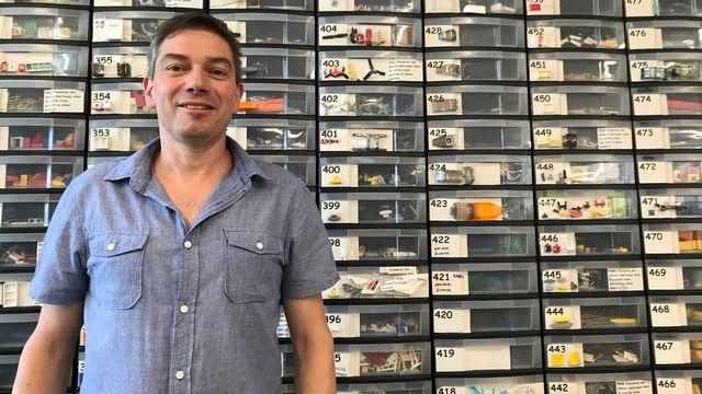Christophe Durussel, fondateur de Brick Occasion SA, pose devant des centaines de tiroirs de pièces détachées de Lego.  [Kim de Gottrau - RTS]