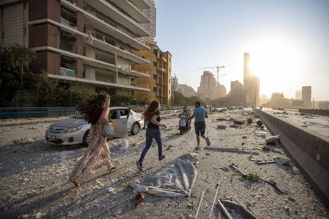 Residents flee the scene of the explosion. [AP Photo/Hassan Ammar - Keystone]