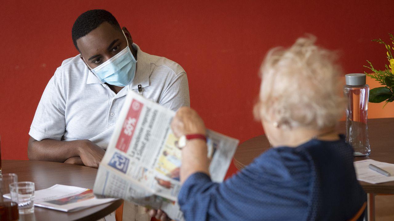Un soldat des troupes sanitaires de l'armée suisse en discussion avec une personne âgée dans un établissement médico-social. [Laurent Gillieron - Keystone]