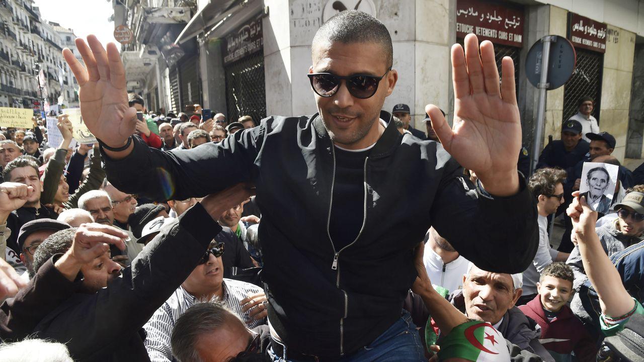 Une photo du journaliste Khaled Drareni, le 6 mars, acclamé par les manifestants après une première arrestation par la police. [Ryad Kramdi  - AFP]