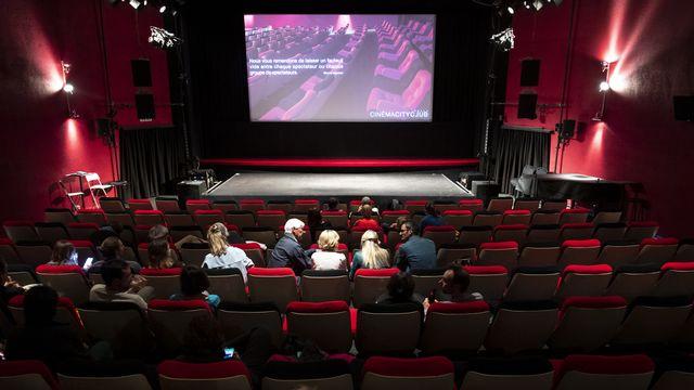 """Des personnes s'installent avant de visionner le film """"L'île aux oiseaux"""" dans la salle de projection du Cinema CityClub le jour de sa réouverture lors de la pandémie de Coronavirus (Covid-19) le 6 juin 2020 à Pully près de Lausanne. [Laurent Gillieron - Keystone]"""