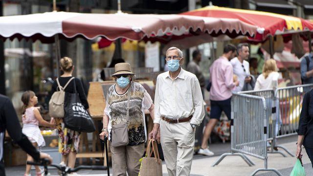 En Suisse, le port du masque n'est obligatoire nulle part en extérieur (ici au marché à Lausanne). [Laurent Gilliéron - Keystone]