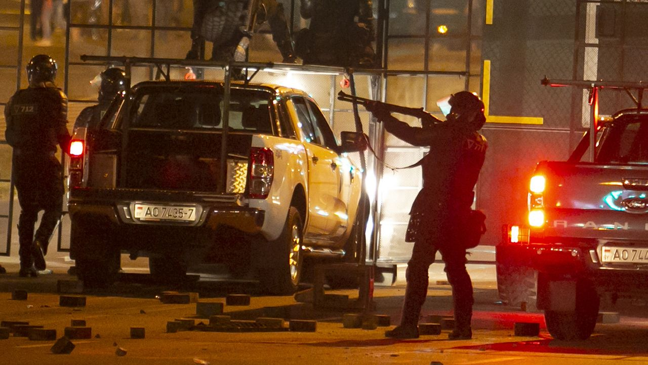 Un policier armé d'un fusil semble mettre en joue des manifestants à Minsk, lundi 10.08.2020. [AP/Keystone]