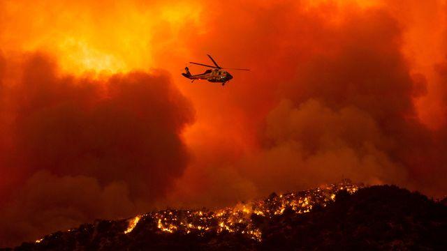 Un hélicoptère se prépare à déverser de l'eau sur le feu du Lake Hugues, au nord de Santa Clarita. Californie, le 12 août 2020. [Ringo H.W. Chiu - Keystone/AP Photo]