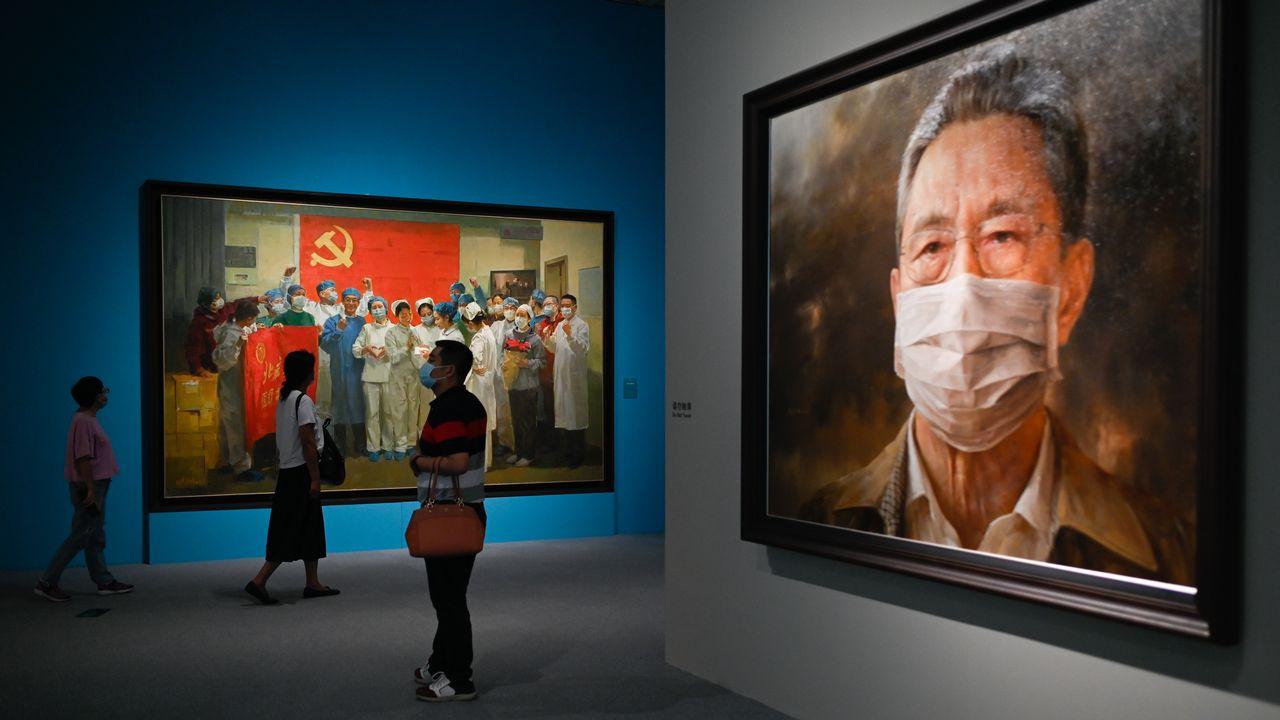 Des gens visitent une exposition sur le coronavirus à Pékin. On peut notamment voir ici, un tableau du célèbre pneumologue Zhanh Nanshan (à droite) réalisé par l'artiste Feng Zhaoxie. [STR - afp]