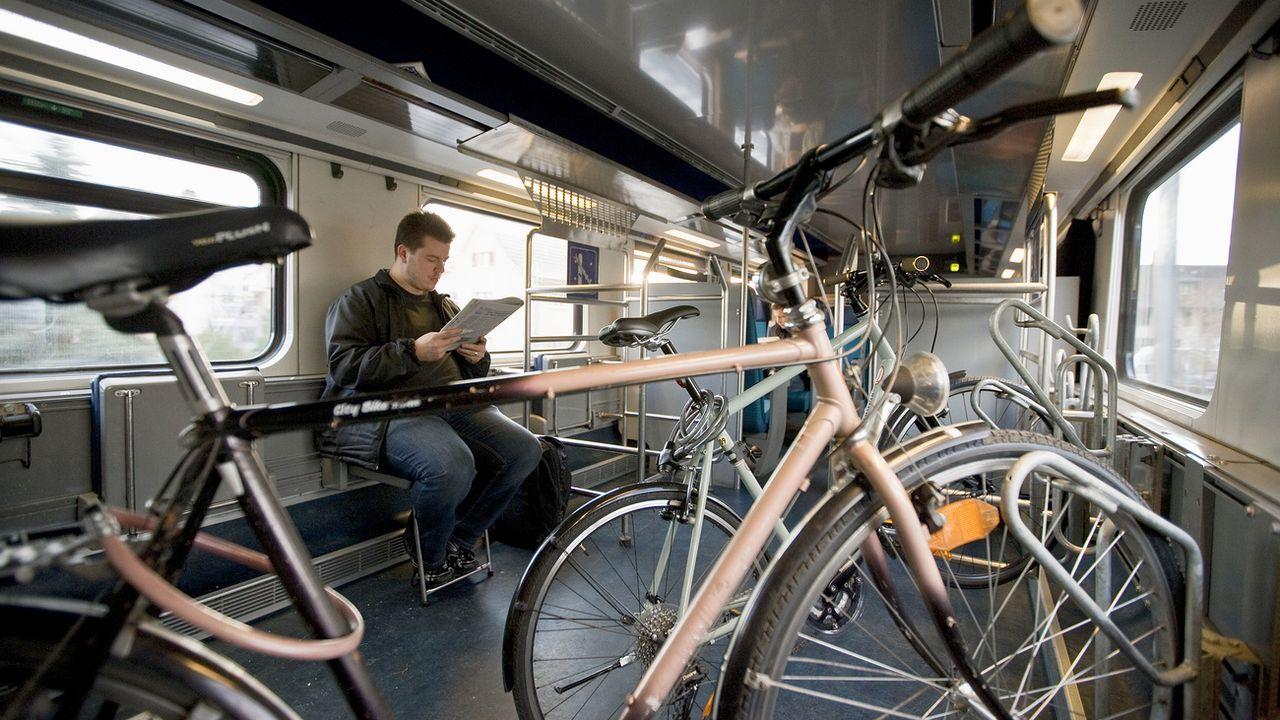 Un homme dans le compartiment destiné aux vélos dans un train CFF. [Gaetan Bally - Keystone]