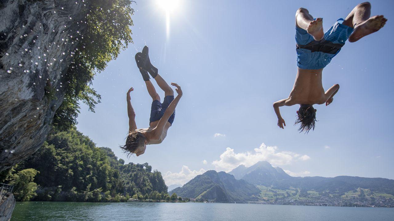 Deux garçons plongent dans le lac des Quatre-Cantons, le 24 juin 2020 à Stans (NW). [Urs Flueeler - Keystone]