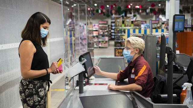 Port du masque pour une employée et une cliente de la Migros. [Jean-Christophe Bott - Keystone]