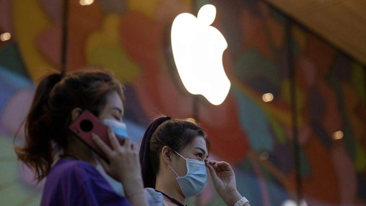 Deux femmes devant un Apple Store à Pékin. [NgHan Guan - Keystone/AP Photo]