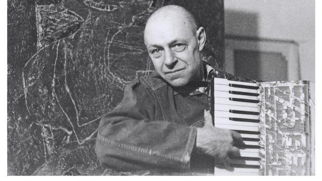 """Jean Dubuffet avec un accordéon devant """"le Violoniste"""". [Luc Fournol - Archives Fondation Dubuffet,]"""