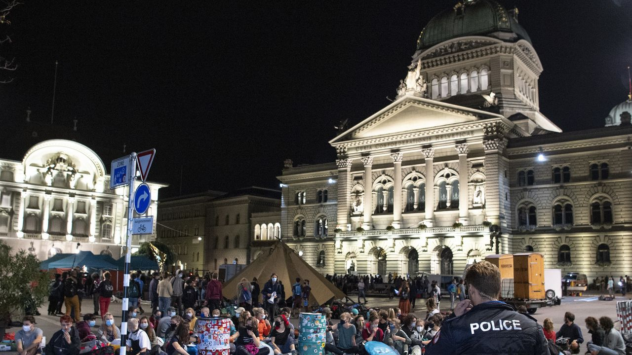 Des manifestants et manifestantes ont investi la Place fédérale à Berne lundi tôt dans la matinée. [Peter Schneider - Keystone]
