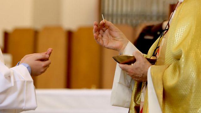 Main de l'évêque qui dispense la Sainte Eucharistie pendant la communion. [ChiccoDodiFC - Depositphotos]