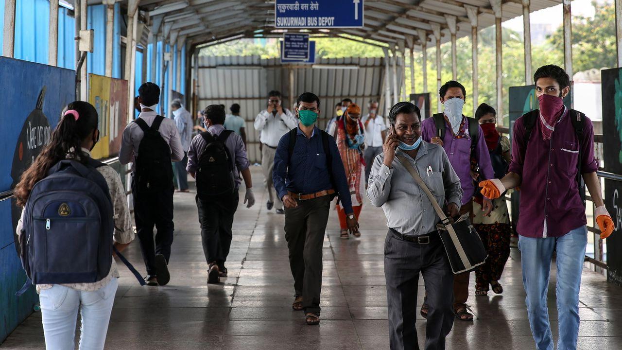 Des personnes dans une gare de Bombay. [EPA/Divyakant Solanki - Keystone]