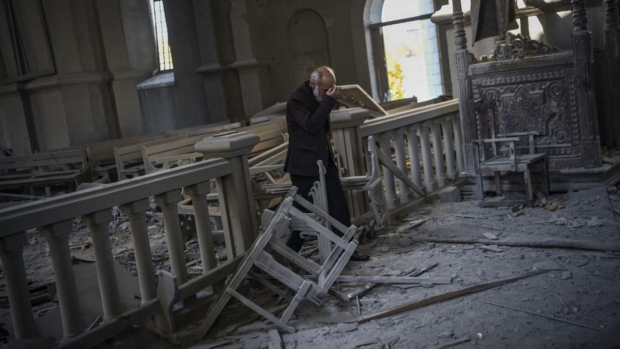 Un homme prie dans la cathédrale endommagée Ghazanchetsots de Shusha, à 15 kilomètres de la ligne de front. [Aris Messinis - AFP]