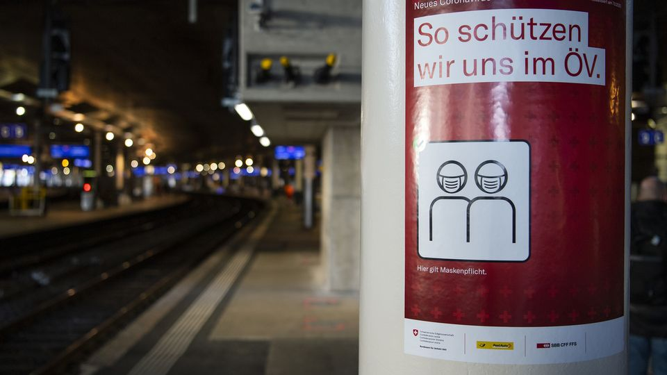 Une affiche pour le port du masque en gare de Berne. [Peter Schneider - Keystone]