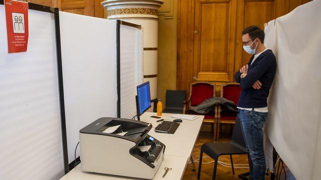 Un scrutateur scanne les bulletins de vote lors des élections communales à Neuchâtel. [Jean-Christophe Bott  - Keystone]