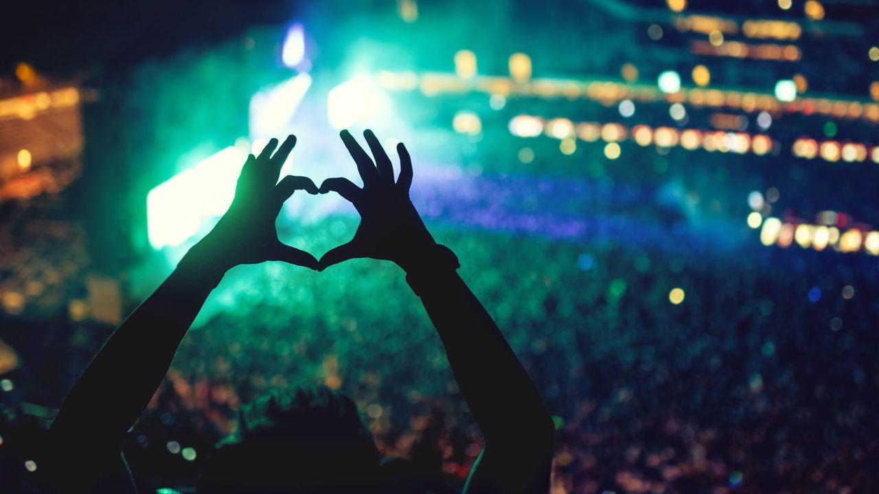 Une personne forme un coeur avec ses mains devant une scène de concert. [bogdan.hoda - Depositphotos]