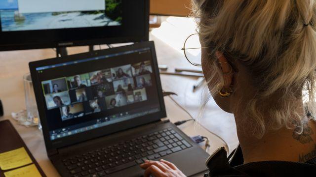Une enseignante d'école primaire donne sa classe par vidéoconférence. [Christian Beutler - Keystone]