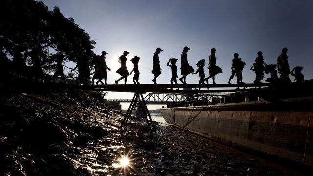 Des enfants déchargent du gravier d'un bateau au Myanmar. [AP/Gemunu Amarasinghe - Keystone]