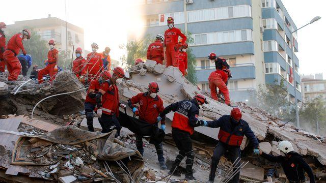 Des secouristes sortent un corps d'un immeuble détruit de la ville d'Izmir. [Reuters]