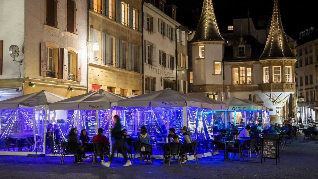 Des personnes assises à la terrasse d'un bar à Neuchâtel, le 25 octobre 2020. [Jean-Christophe Bott - Keystone]