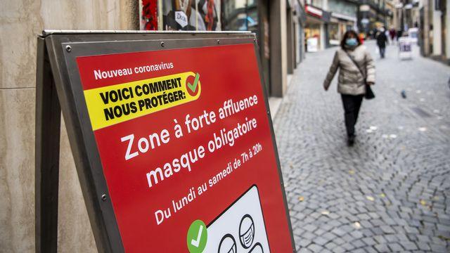"""Une personne masquée près d'un panneau signalant une """"zone à forte affluence"""", au centre-ville de Lausanne, le 10 novembre 2020. [Jean-Christophe Bott - Keystone]"""