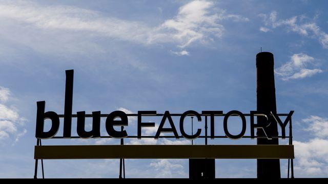 Le logo de Blue Factory derrière la cheminée de l'ancienne brasserie Cardinal à Fribourg. [Jean-Christophe Bott - Keystone]