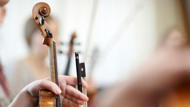 Gros plan du cou d'un violon avec un arc. [sw_stock - depositphotos]