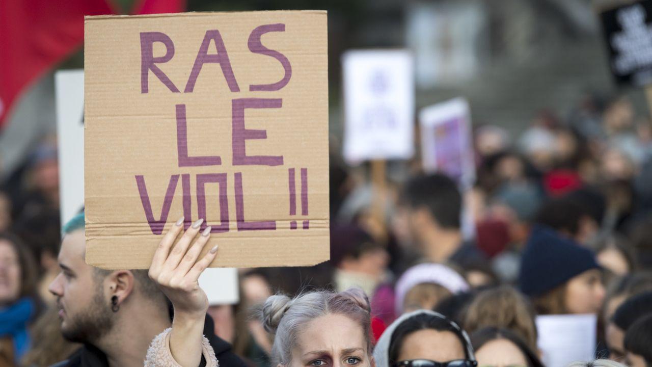 """Une femme brandit une pancarte """"Ras le viol!!"""" lors d'une manifestation contre les violences sexistes et sexuelles, le 23 novembre 2019, à Lausanne.  [KEYSTONE/Laurent Gillieron - Keystone]"""